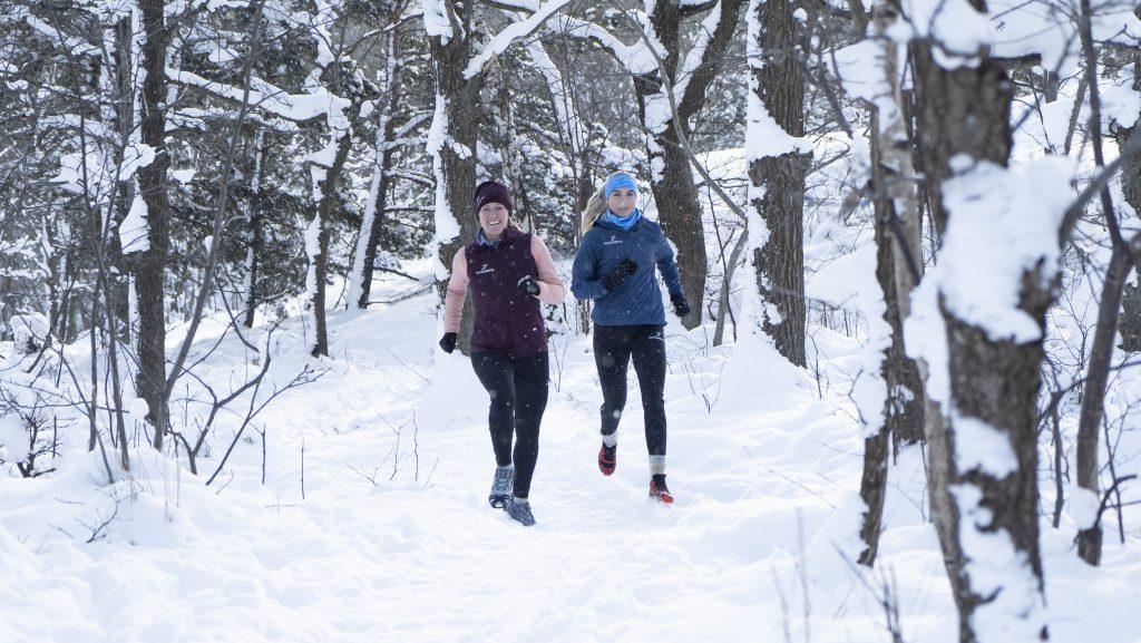 två tjejer springer i snön