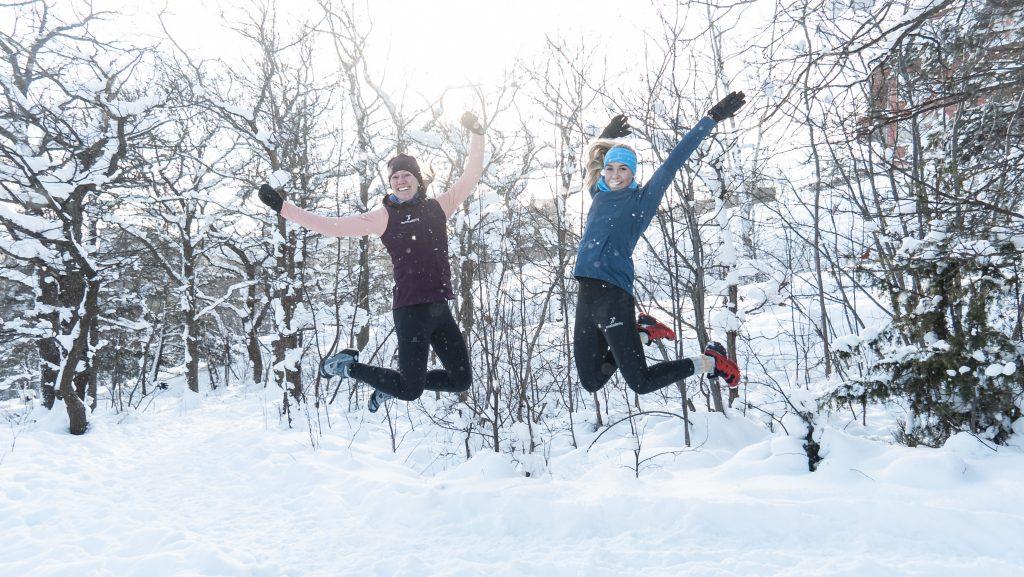 Två glada tjejer hoppar i snön