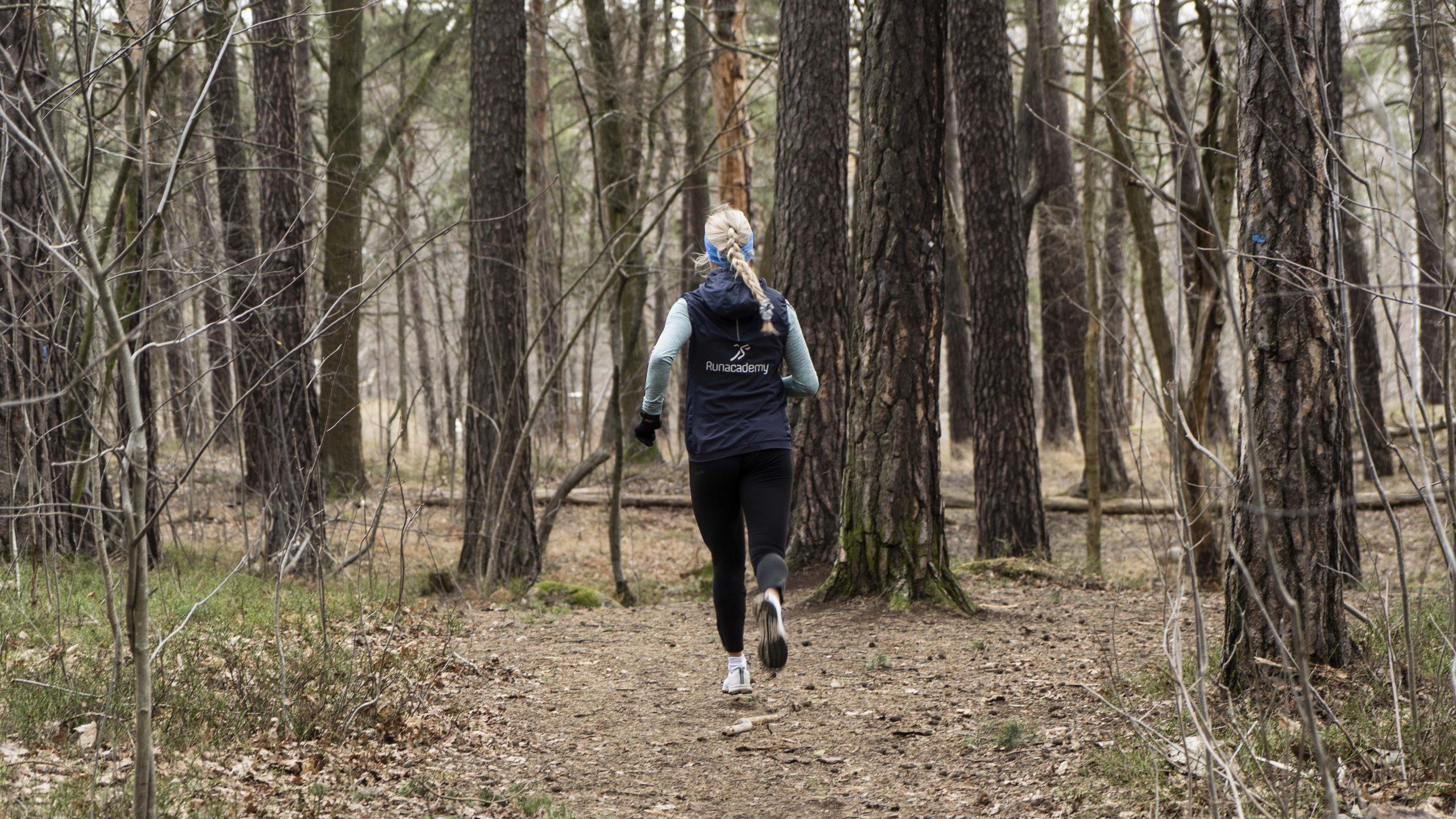 Tjej springer i skogen